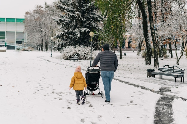 Father with child and baby walking with stroller in winter snow park.