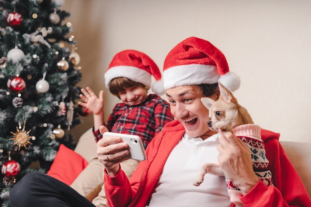 Father with child and puppy dog in santa hats having a video chat