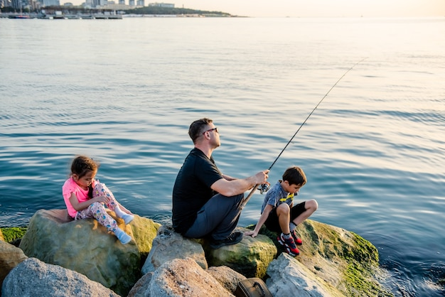 Father with children on a fishing trip by the sea children fish over a cliff in the sea