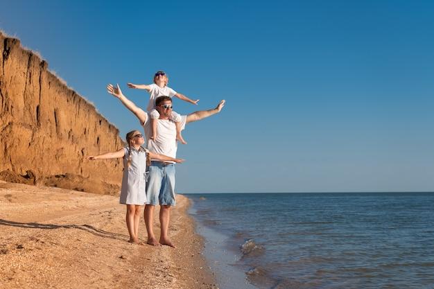 Отец с детьми весело на пляже в дневное время.