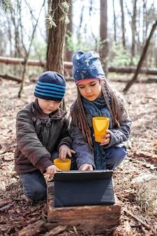 森を歩いているおばあちゃんとつながり、オンラインでビデオレポートを見せている子供を持つ父親