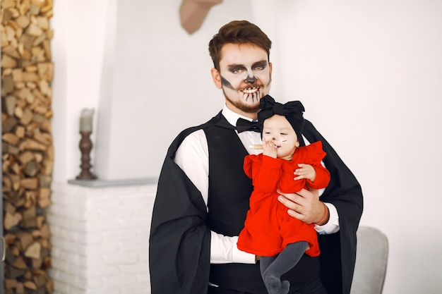 Father with daughter in costumes and makeup. family prepare to celebration of halloween.