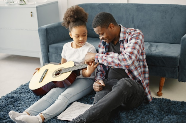 Father with daughter on couch. girl holding a guitar. learning guitar.