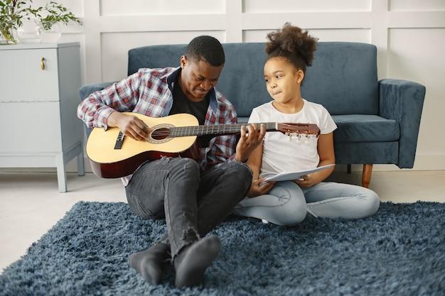 ソファの上に娘を持つ父。ギターを持っている女の子。ギターを学ぶ。