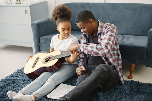 소파에 딸과 함께 아버지입니다. 기타를 들고 소녀입니다. 기타 학습.