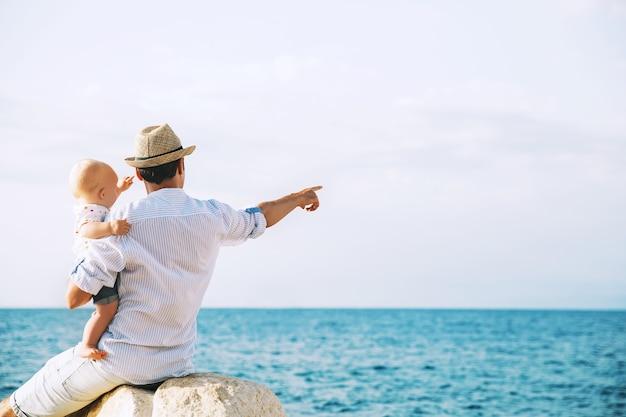 海と空の背景に娘を持つ父男と赤ちゃんは前方に指摘されています