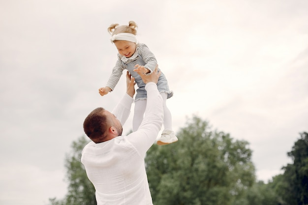 Отец с дочерью, играя в парке летом