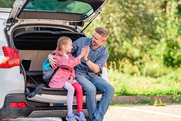 Father with daughter sitting on car trunk after schooling