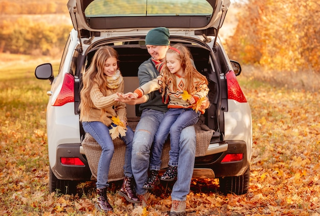 Father with daughters in autumn surroundings