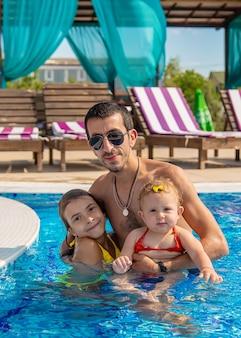 Отец с дочерьми в бассейне. выборочный фокус. ребенок.