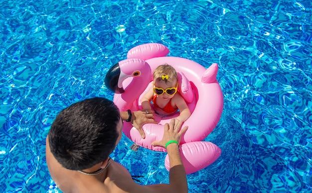 プールで娘を持つ父。セレクティブフォーカス。子。