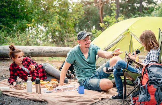 森のテントの近くでピクニックに娘を持つ父