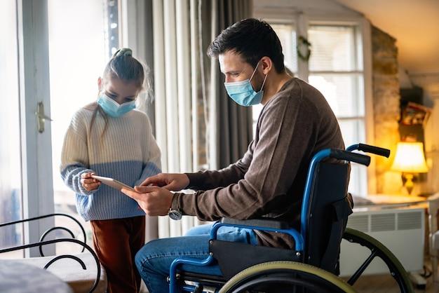 マスクを着用しながら子供と一緒に自宅でタブレットを使用して車椅子の障害を持つ父親。人々の教育技術コロナウイルスの概念