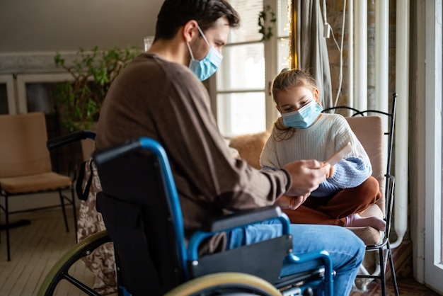 Father with disability in wheelchair using tablet at home with child while wearing masks. people education technology coronavirus concept