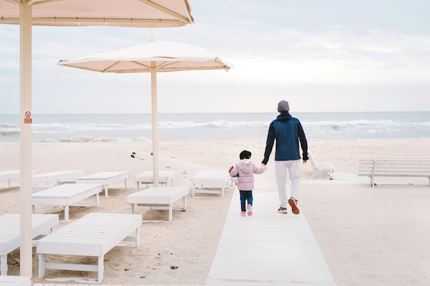 Father with girl child walking to sea beach in autumn