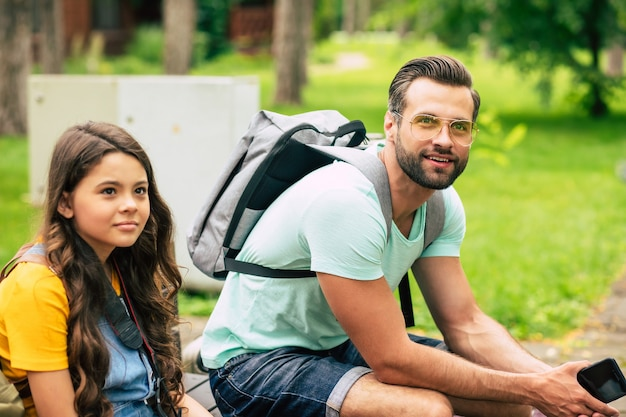 Father with gray backpack and little daughter