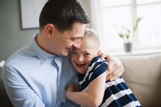 A father with happy down syndrome son indoors at home, hugging and laughing.