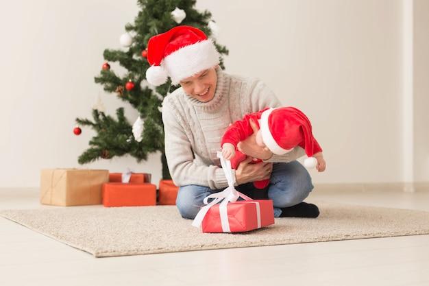 クリスマスを祝うサンタの帽子をかぶった男の子を持つ父。