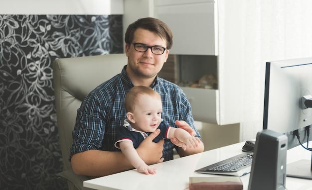 彼の赤ん坊の息子がオフィスで働いている父