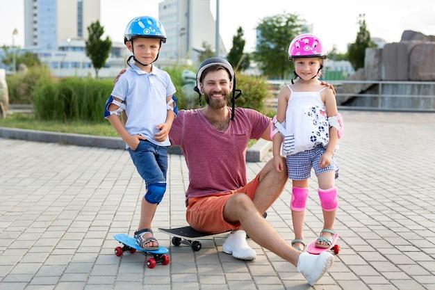 父は子供たち、息子と娘と一緒に公園でスケートをし、笑顔でカメラを見ます。