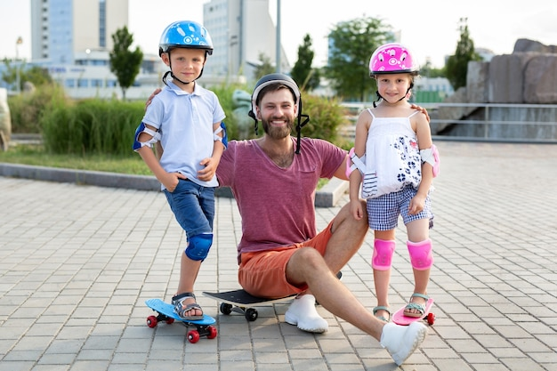 Father with his children, son and daughter, skate in the park, smile and look at the camera.