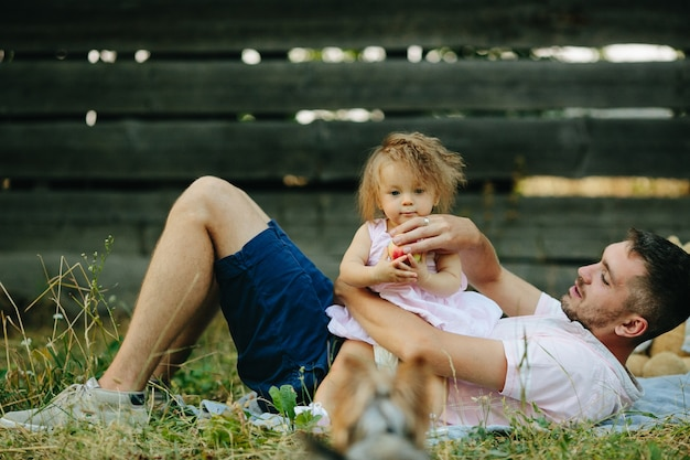 Father with his little daughter sitting on his belly