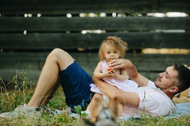 Отец с его маленькая дочь сидит на животе