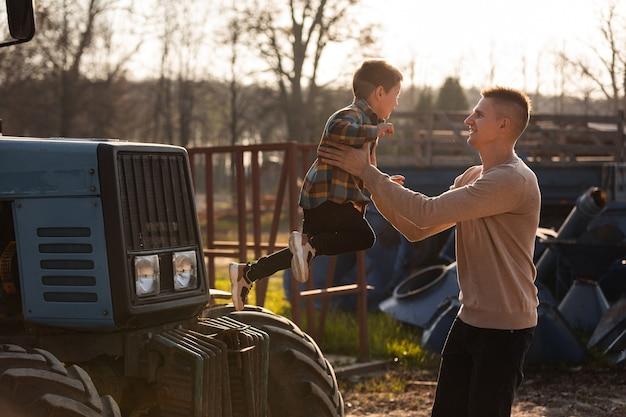 晴れた秋の日にトラクターの近くの農場で楽しい時間を過ごしている彼の幼い息子を持つ父