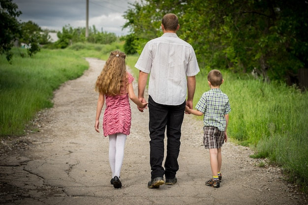 Father with his son and daughter walking along the road