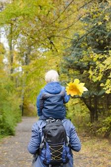 秋の森を歩く息子と肩を組んだ父。背面図