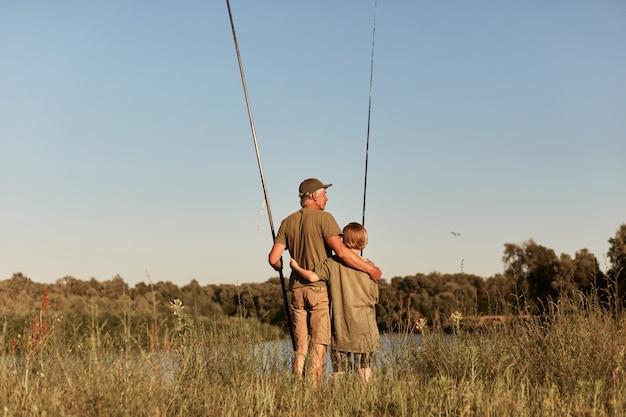 湖での屋外釣り、釣り竿のビンの手を握り、湖の近くに立って休憩し、カジュアルな服を着ている息子を持つ父は、魚を捕まえたいと思っています。
