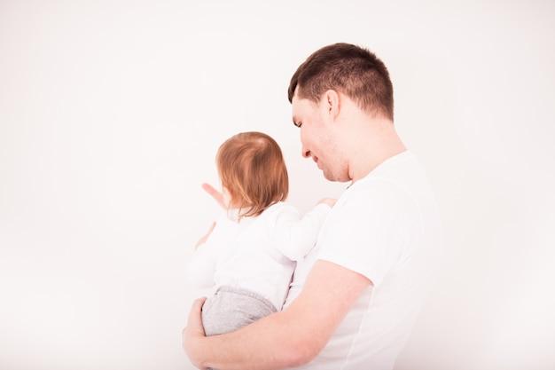 白い背景の上の彼の幼児の女の赤ちゃんと父