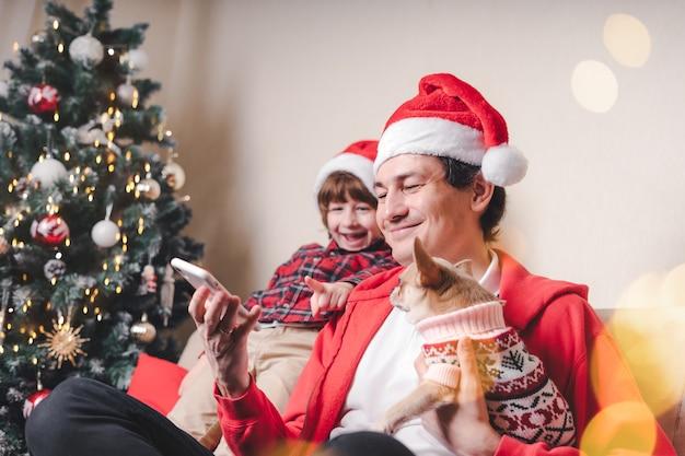 Отец с ребенком и щенком в шляпах санты, держа сотовый телефон