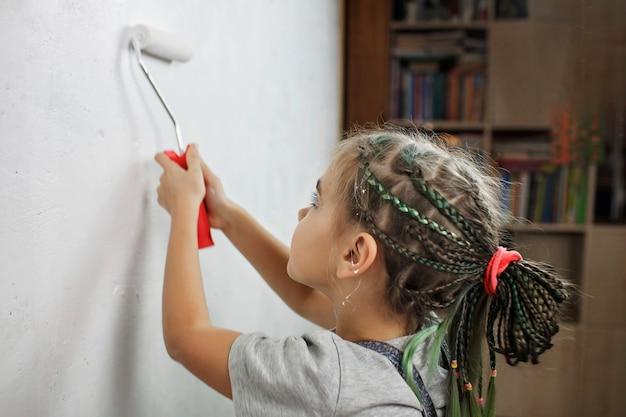 Отец с ребенком вместе ремонтируют комнату и вместе красят стену