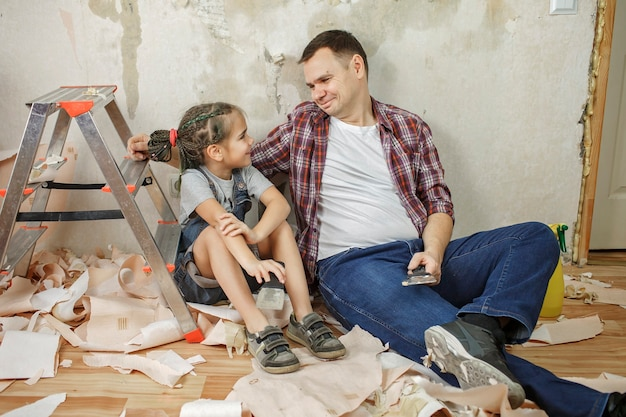 Отец с ребенком вместе ремонтируют комнату и вместе снимают обои
