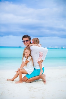 Father with kids on the beach enjoying summer. family vacation