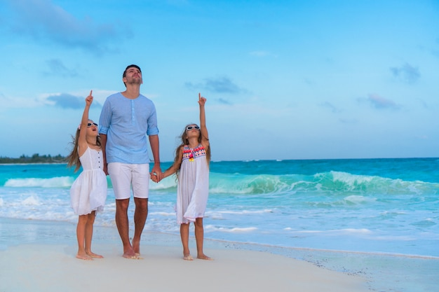 Father with kids on the beach on sunset