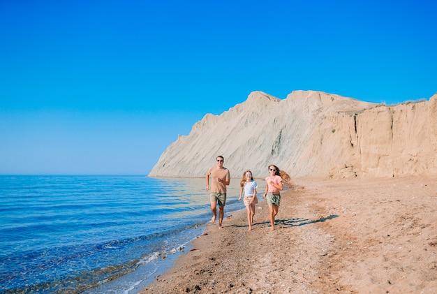 Отец с детьми на пляже, наслаждаясь летом