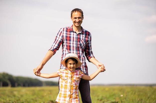 Отец с маленькой дочерью, играя на лугу