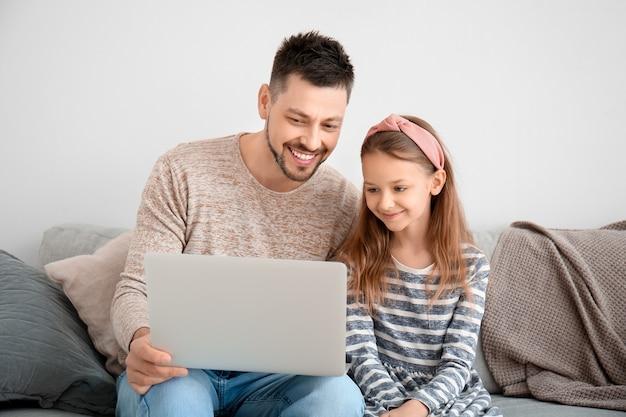 家でおしゃべりする小さな娘のビデオを持つ父