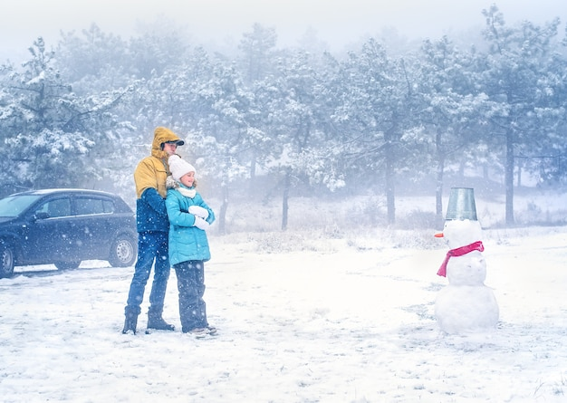A father with a little daughter in winter clothes are hugging each other in the forest and looking at the snowman.
