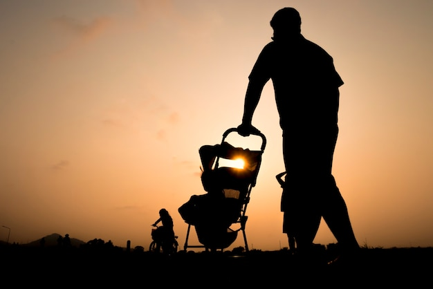 Father with little son and daughter walking at sunset