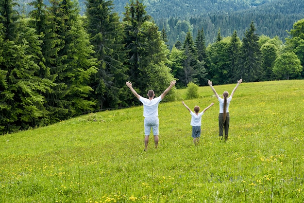 Father with little son and mother stand raising hands on a green field