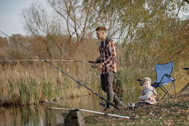 Father with little son near river in a morning fishing