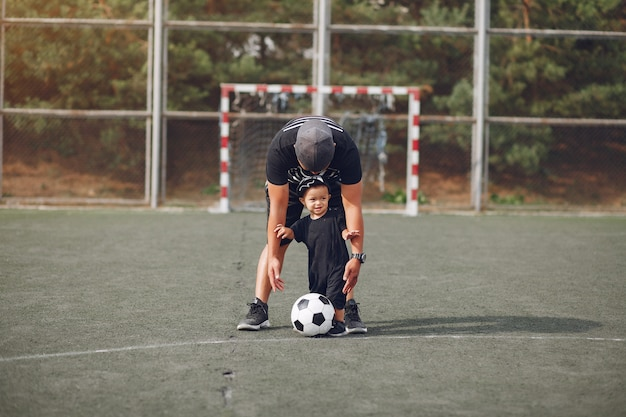 Father with little son playing football