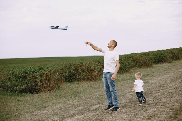 おもちゃの飛行機で遊んでの幼い息子を持つ父