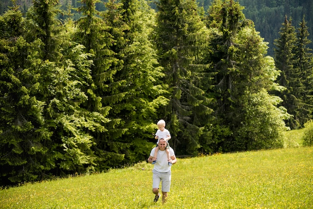 Father with little son on shoulders walking on a green meadow