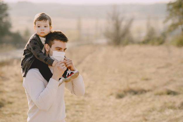 マスクを身に着けている幼い息子を持つ父