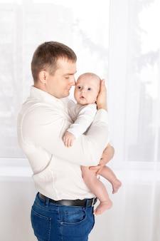 窓際に生まれたばかりの赤ちゃんを持つ父、幸せな愛情のある家族の概念、父の日