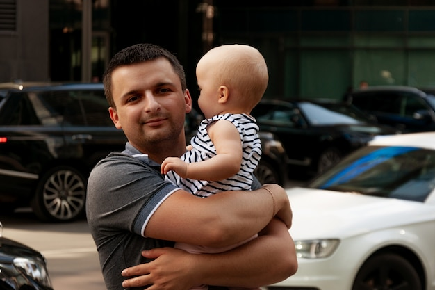 Father with one year old baby in his arms. walk in an urban environment.